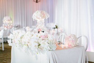 sweetheart-table-with-white-linen-front-of-table-lined-with-lush-display-of-orchids-and-ivory-roses