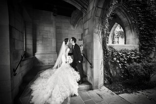 black-and-white-photo-of-bride-and-groom-kissing-stone-walls-greenery-classic-chicago-wedding