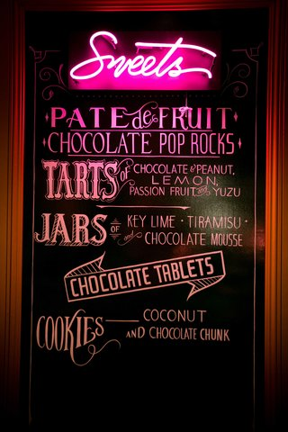 chalkboard-with-neon-sign-displaying-sweets-at-dessert-bar