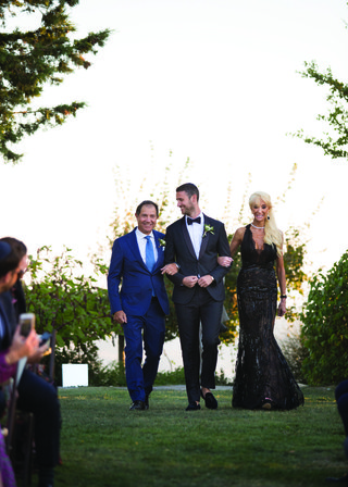 groom-in-classic-black-suit-escorted-down-the-aisle-by-father-in-blue-suit-and-mother-in-black-gown