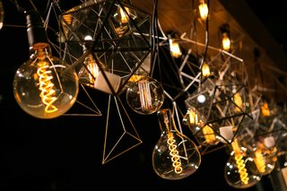 a-unique-lighting-concept-with-hanging-light-bulbs-and-geometric-shapes-suspended-from-wooden-board