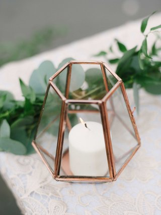 small-white-candle-in-mirrored-geometric-terrarium-on-white-lace-table-linen-with-greenery