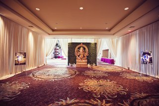 indian-hindu-wedding-gold-statue-of-ganesha-in-front-of-wall-of-greenery-pictures-of-couple
