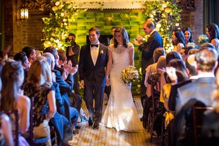 wedding-ceremony-bride-and-groom-walk-up-aisle-hand-holding-green-backdrop-yellow-flowers-white
