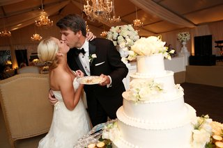 bride-and-groom-kissing-beside-wedding-cake-cake-eating-tradition