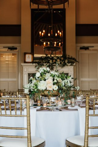 wedding-reception-in-room-with-fireplace-chandelier-rustic-tall-mirror-and-low-centerpiece
