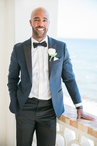 groom-on-balcony-in-mexico-in-blue-and-black-tuxedo-with-bow-tie