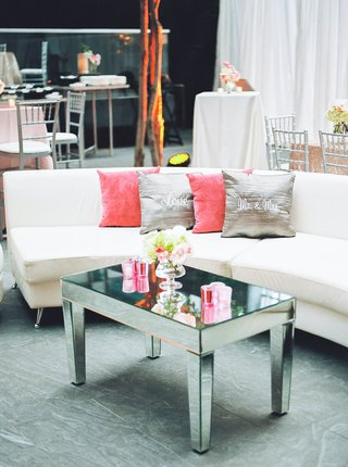 white-pink-lounge-pink-gray-pillows-mirror-coffee-table-pink-candles-low-arrangement