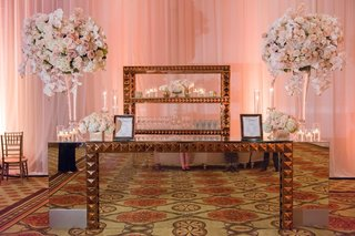ballroom-wedding-reception-mirror-bar-with-pyramid-studs-gold-two-large-flower-arrangements-roses