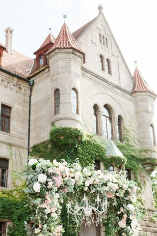 wedding-ceremony-germany-castle-venue-greenery-white-pink-flowers-chandelier-arch-chuppah