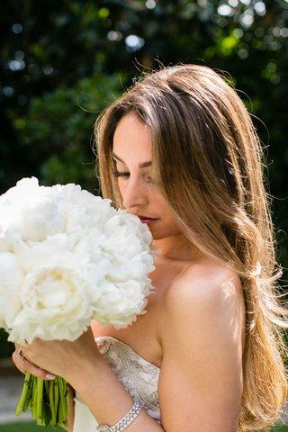 bride-with-long-hair-and-strapless-oscar-de-la-renta-wedding-dress-sniffs-white-peony-bridal-bouquet