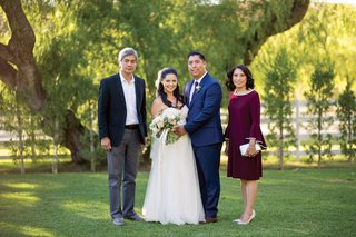father-of-groom-and-mother-of-groom-with-couple-santa-susana-california-wedding-ranch-burgundy-dress