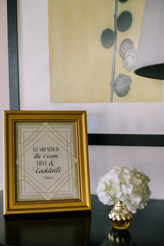 sign-with-art-deco-design-saying-all-you-need-is-the-ocean-love-cocktails-at-wedding-reception