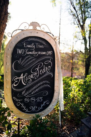 a-black-and-white-sign-with-couples-names-in-calligraphy-outside-ceremony-space