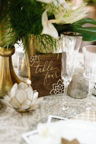 dark-wood-walnut-table-number-with-moroccan-flower-design-and-gold-lettering-modern-calligraphy