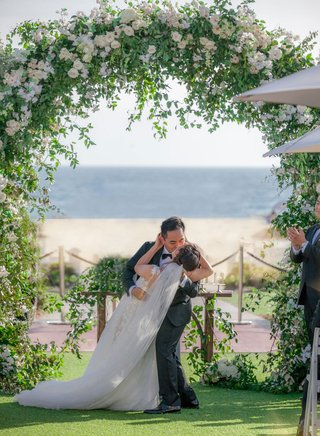 groom-dips-bride-for-a-kiss-during-ceremony-under-tall-floral-arch