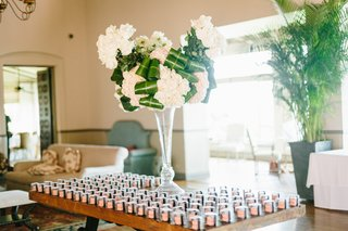 escort-card-table-with-macaron-favors-floral-arrangement-with-folded-leaves