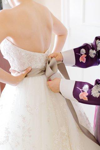 tying-bow-on-wedding-dress