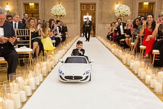 wedding-ceremony-ring-bearer-driving-down-aisle-in-miniature-maserati-car-candles-guests