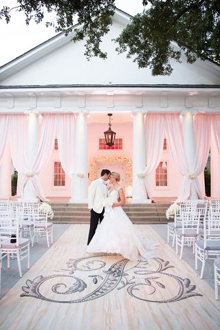 wedding-portrait-in-front-of-ceremony-decor-large-monogram-on-aisle-runner-pink-drapes-white-chairs