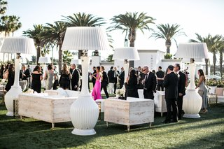 outdoor-cocktail-hour-with-large-heat-lamps-that-look-like-lamp-shades-wood-furniture-whitewash