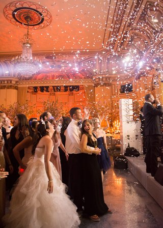 wedding-guests-including-the-bride-watch-the-stage-as-confetti-falls-during-ceremony