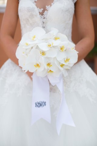 bride-holding-small-bouquet-of-all-white-phalaenopsis-orchid-flowers-and-ribbon-with-monogram