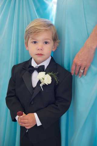 blond-ring-bearer-in-tux-with-red-lollipop
