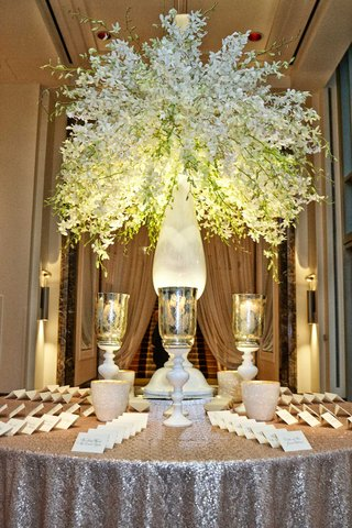 escort-card-table-with-silver-metallic-linen-table-candles-and-tall-white-green-floral-arrangement