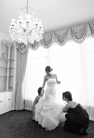 black-and-white-photo-of-a-bridesmaid-and-mother-helping-the-bride-into-her-mermaid-dress