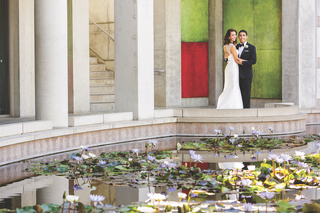 bride-and-groom-embrace-next-to-pond-filled-with-flowers