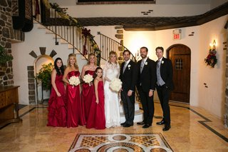holiday-wedding-with-bridesmaids-in-red-dresses-hold-white-rose-bouquets-bride-in-pnina-tornai