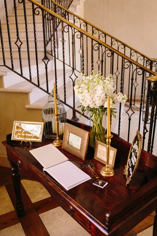 guest-book-table-with-framed-mirror-signs-white-blossoms-bird-cage-gold-taper-candles-candlestick