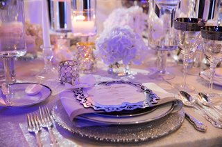 wedding-reception-place-setting-silver-charger-plate-with-menu-card-candles-low-centerpiece-rimmed