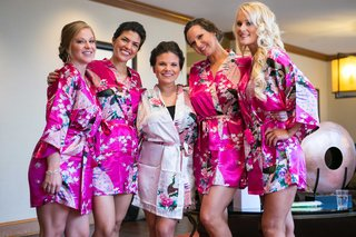 a-bride-in-a-light-pink-robe-with-floral-decorations-posing-with-four-bridesmaids-hot-pink-robes
