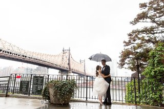 bride-and-groom-in-rain-on-wedding-day-umbrella-couple-portrait-sutton-place-park-in-new-york-city