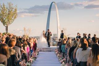 bride-and-groom-at-altar-wedding-ceremony-outside-in-st-louis-gateway-arch-pink-and-white-flowers