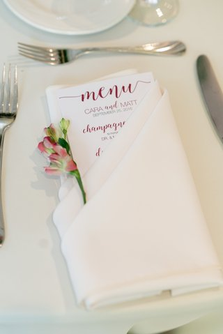 menu-with-burgundy-calligraphy-tucked-into-cream-linen-with-a-blossom