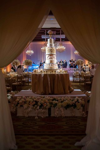 wedding-cake-displayed-on-flower-wrapped-stage-round-gold-linen-table-tall-confection-drapery