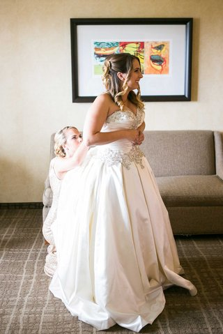 bride-in-allure-ball-gown-helped-into-dress-by-bridesmaid-and-little-sister
