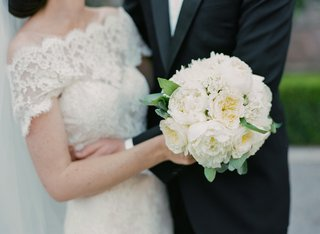 bride-wearing-lace-off-the-shoulder-dress-holding-white-bouquet