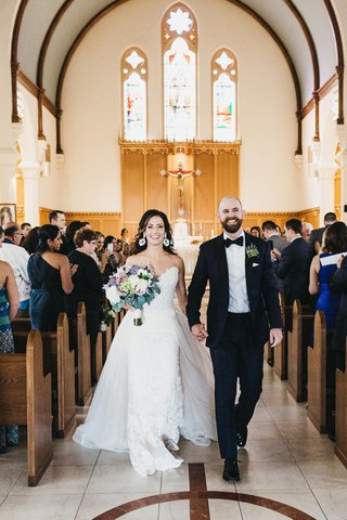 wedding-recessional-in-catholic-church-bride-in-lace-wedding-dress-with-overskirt-groom-in-tux