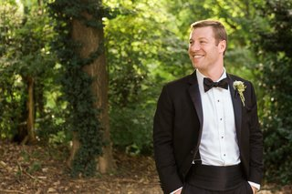groom-in-tuxedo-with-hands-in-pocked-smiling-outside