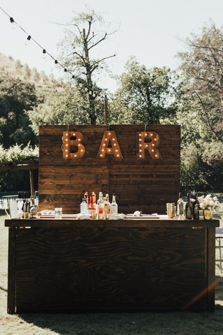 outdoor-wedding-with-wooden-bar-setup-with-bar-marquee-lights