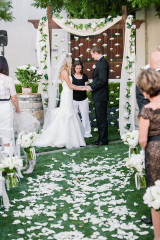 bride-in-a-strapless-hayley-paige-dress-and-veil-with-groom-at-outdoor-ceremony-with-white-flowers