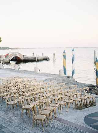 villa-inspired-wedding-in-miami-wood-chairs-set-up-on-walkway-by-water-vizcaya-in-miami