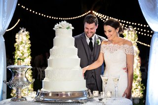 bride-and-groom-cut-six-tier-wedding-cake-with-lace-detail