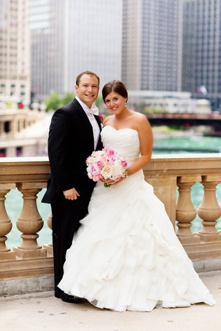 bride-wearing-ball-gown-carrying-pink-bouquet-stands-with-groom-in-front-of-chicago-skyline