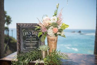 oceanfront-wedding-reception-bar-sign-in-copper-frame-white-hydrangeas-lisianthus-peach-roses