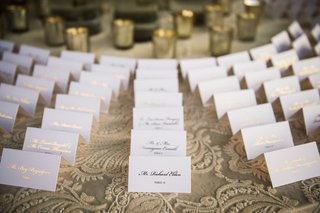 white-wedding-escort-card-with-gold-foil-calligraphy-table-with-lace-linens